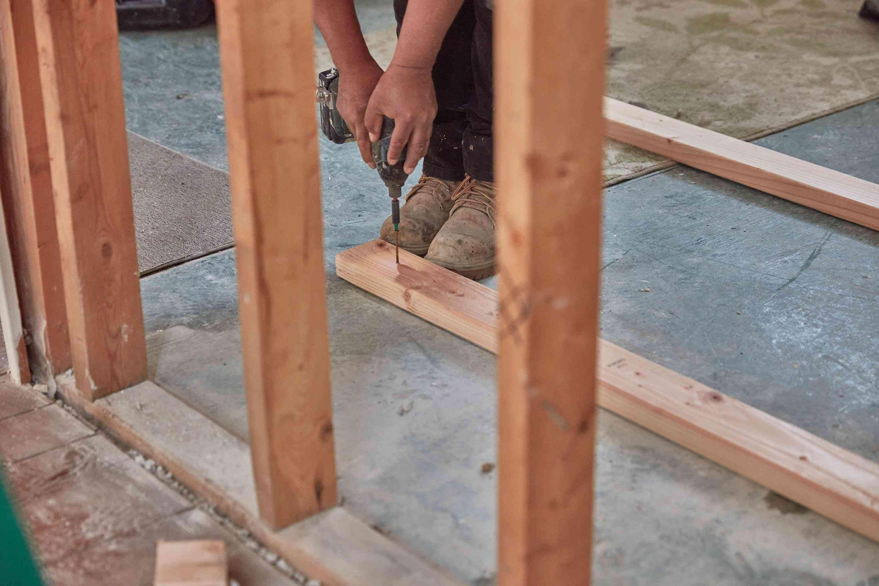 Wood studs being drilled on ground to add extra support for load bearing wall