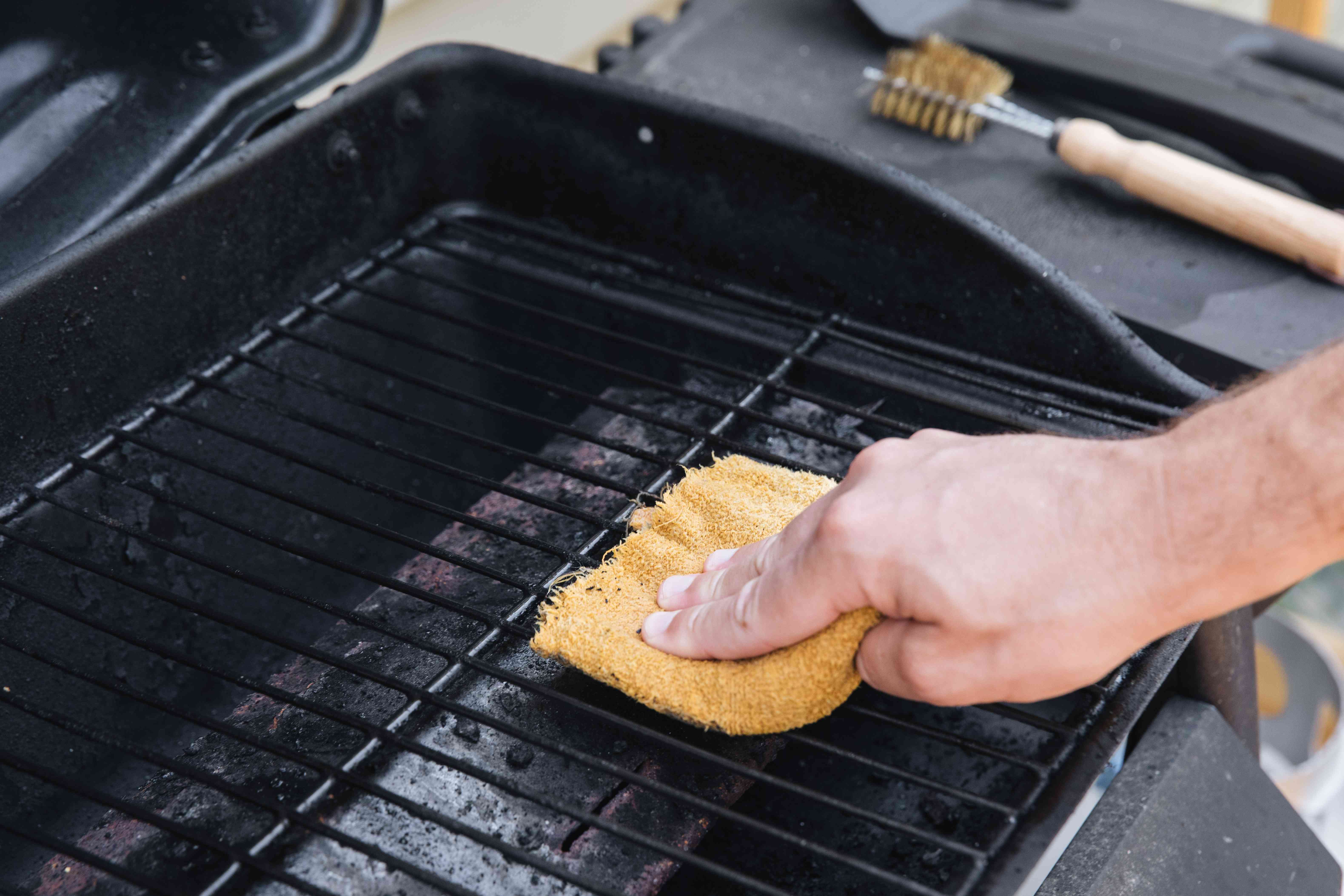 using a scrubber on the grill grates