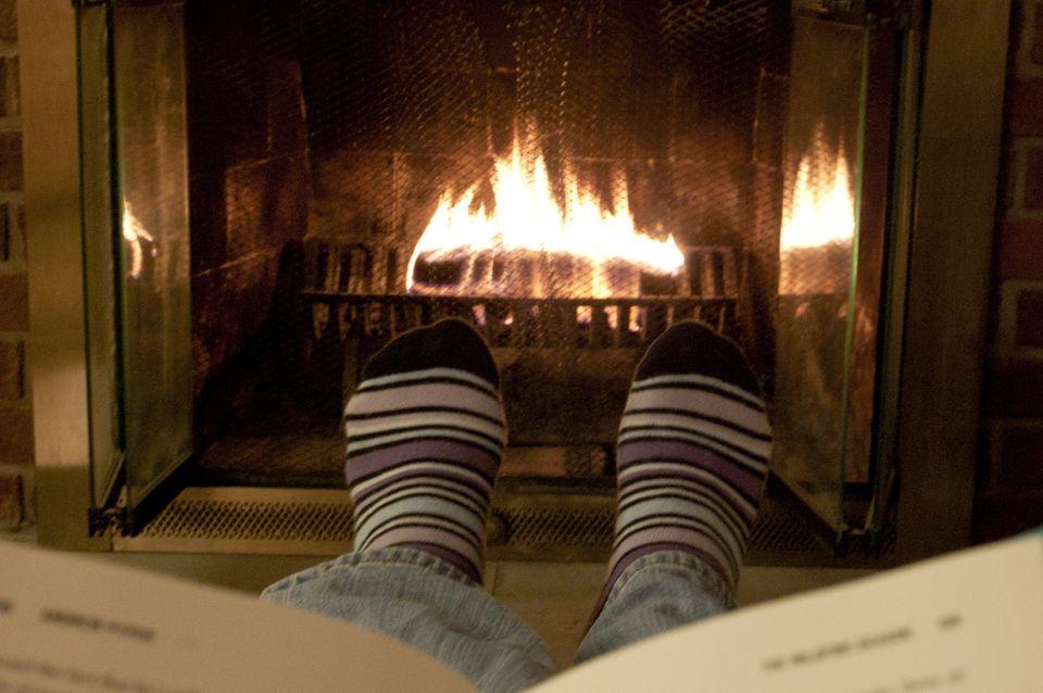 Feet in socks being warmed by a fire in a brick fireplace.