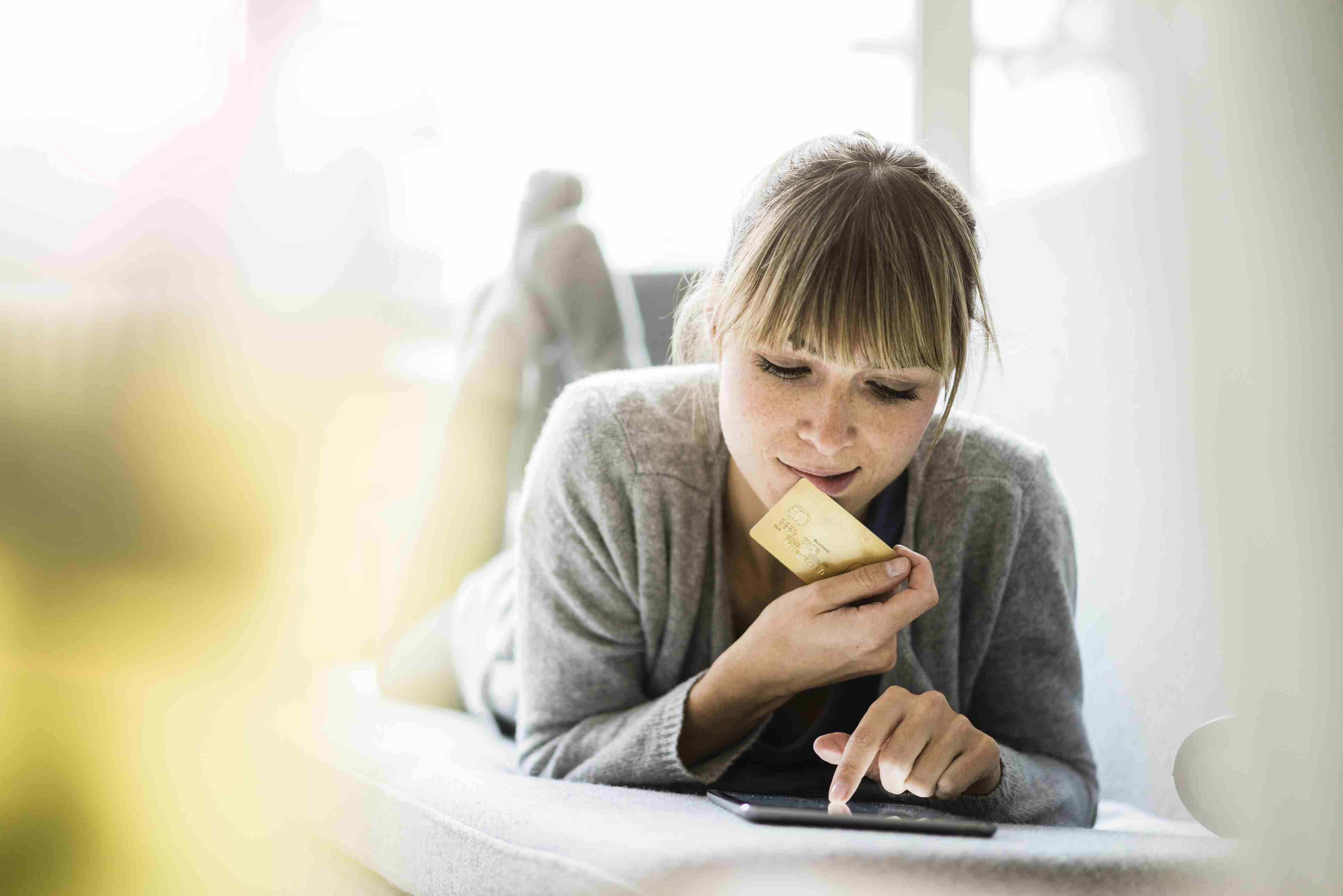 Woman lying on couch with credit card and tablet
