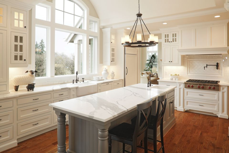 White kitchen cabinets and island with two chairs.
