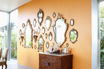 Grouping of antique mirrors on solid wall.