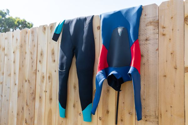 Blue and black wetsuit hanging over wooden fence to air dry