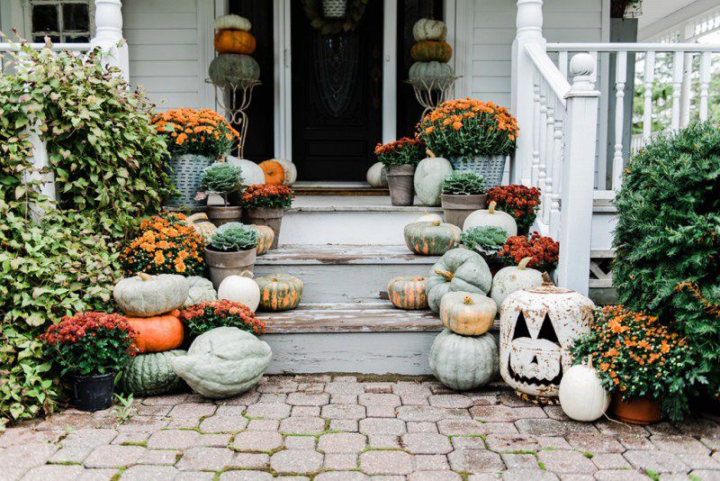 orange and red mums neutral pumpkins front porch
