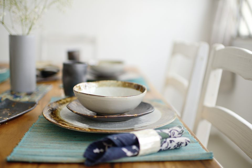 Beautifully set table with handmade ceramic dishes and wooden accents