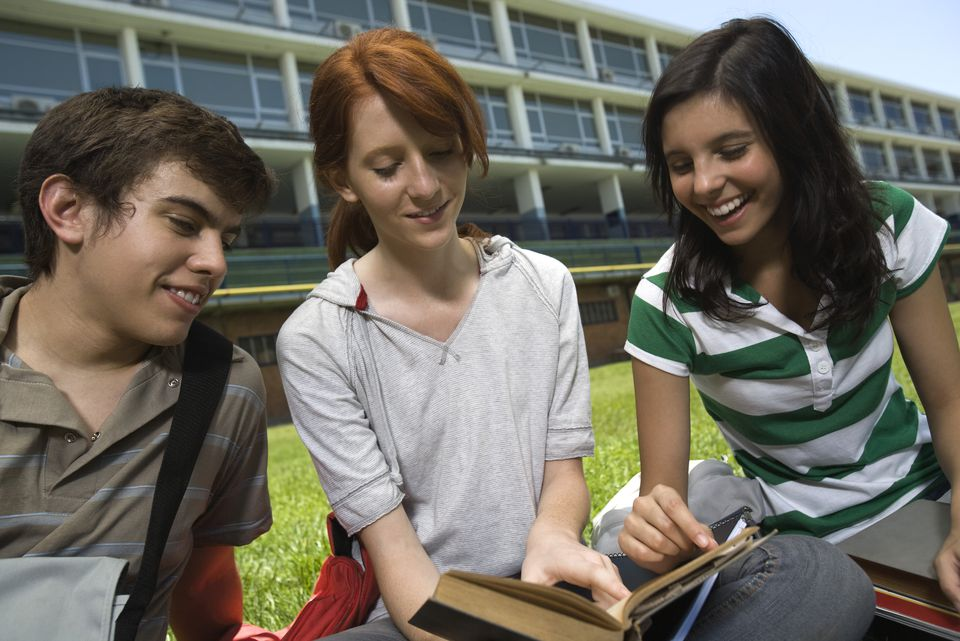 Hight school student showing friends passage in book, sitting together on school lawn