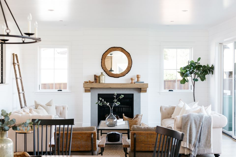 Modern farmhouse living room with wooden mirror over fireplace with windows on each side