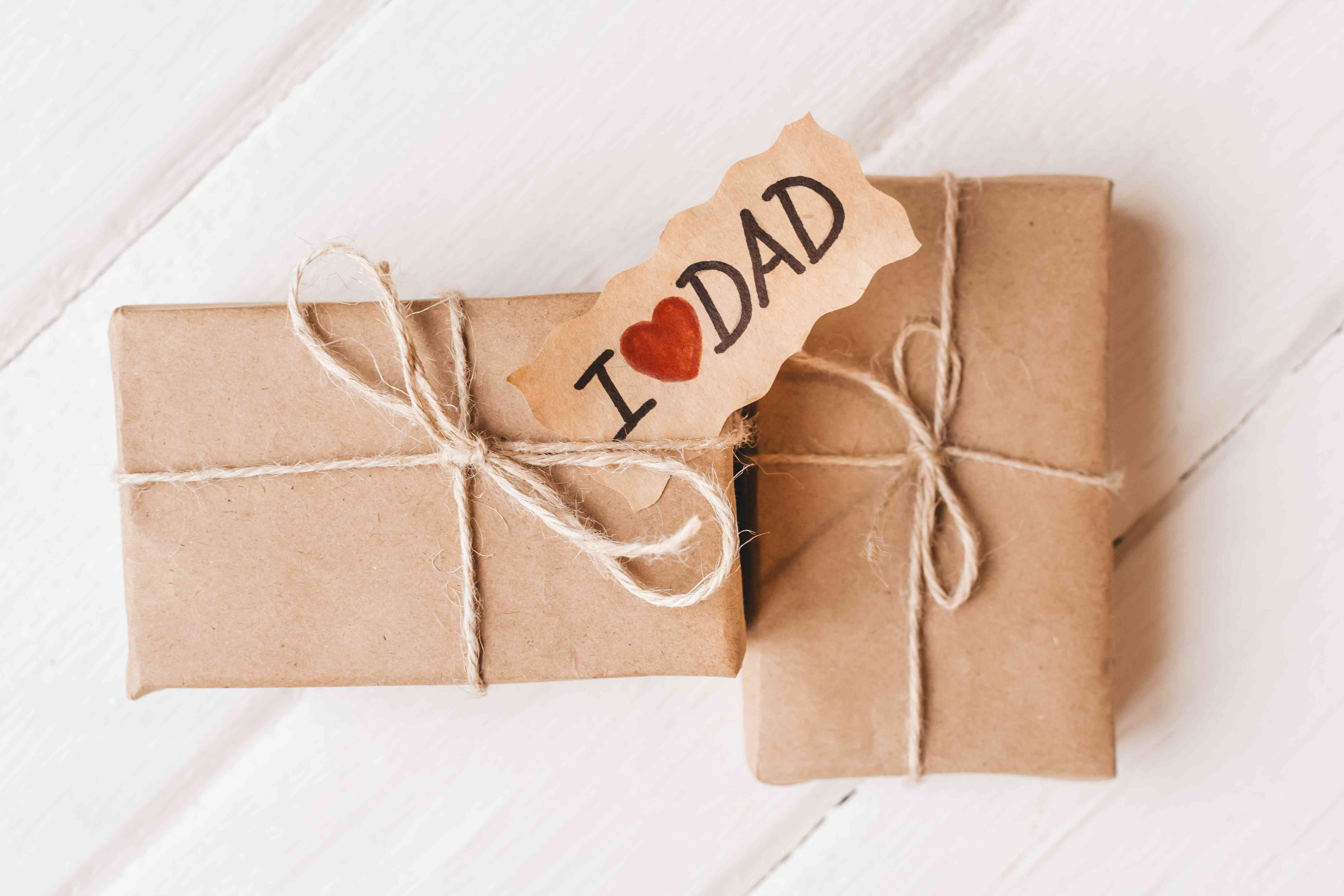 Gift box with a tag on white wooden background. Father's day or birthday concept.