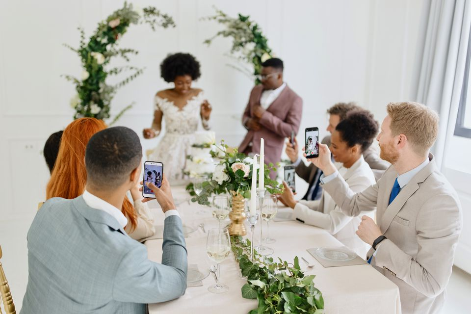 Newlyweds dancing in front of the wedding cake while their friends broadcasting live the wedding ceremony