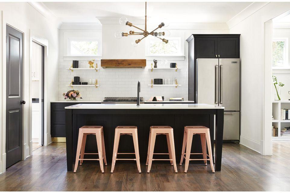 Gabinetes negros con detalles metálicos, azulejos blancos y características de madera