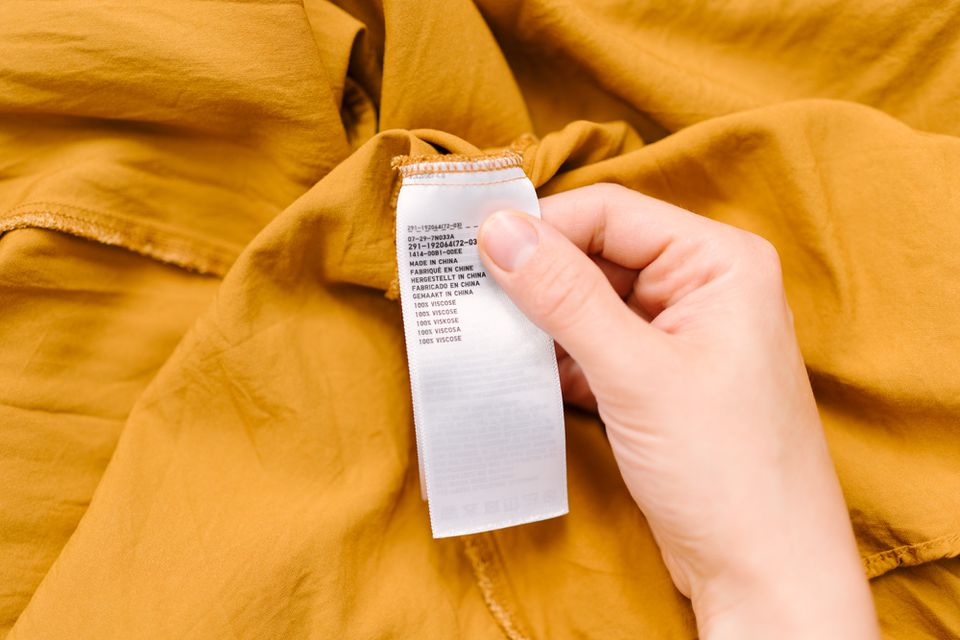 Someone checking the label on a viscose garment