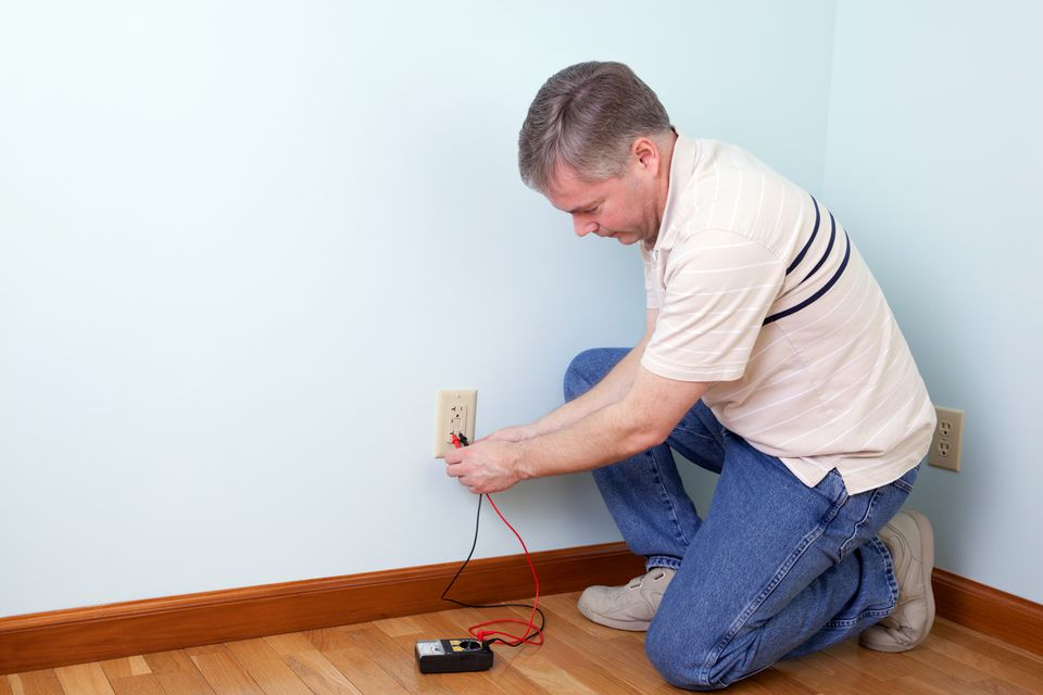 An electrician tests a GCFI outlet after installation