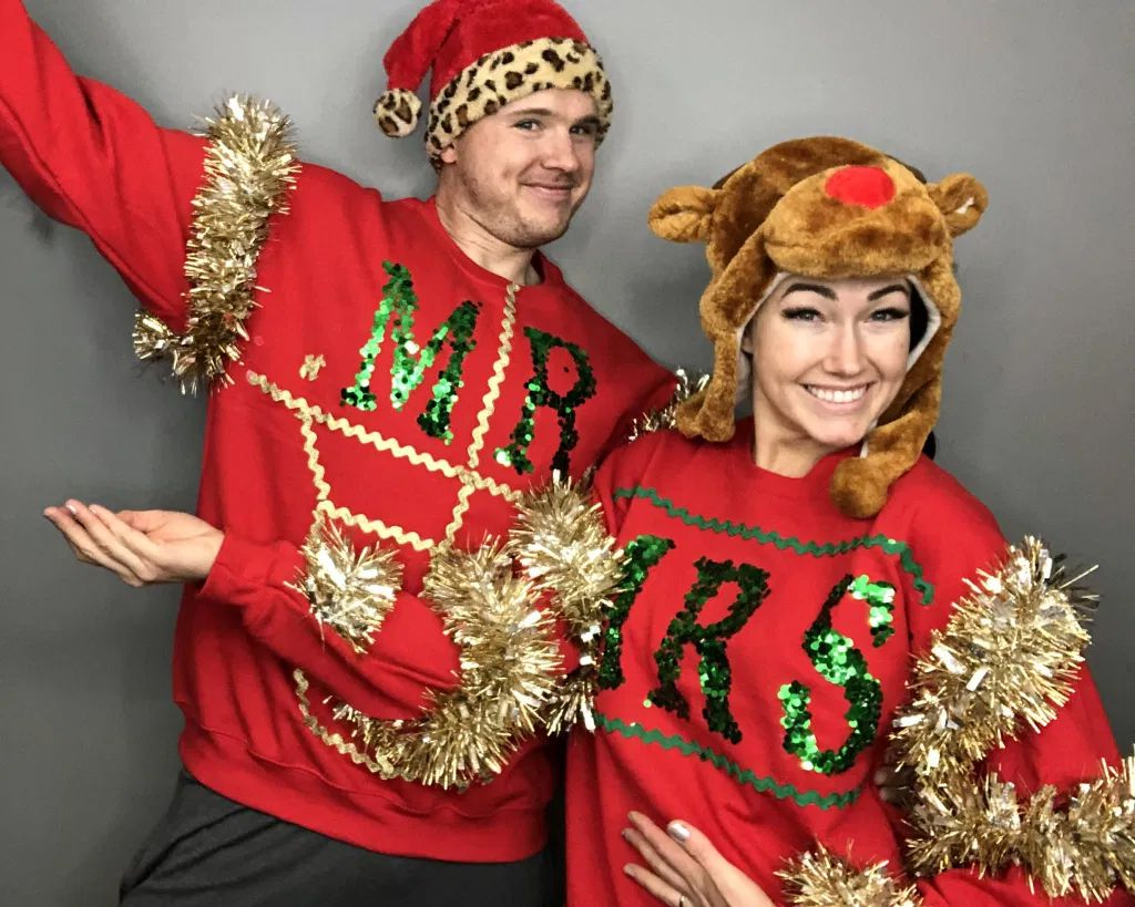 A man and woman wearing ugly Christmas sweaters