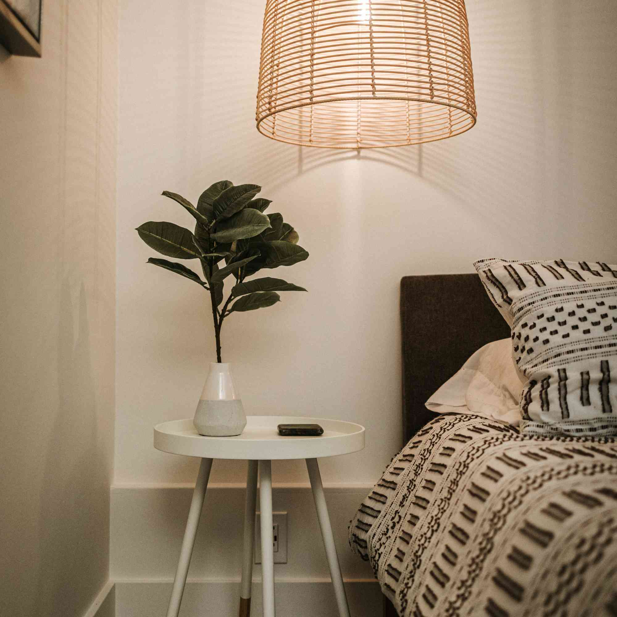 plant on a nightstand in a bedroom with a large light