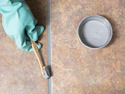 Changing grout color to gray with old toothbrush and green gloves over tiles floor