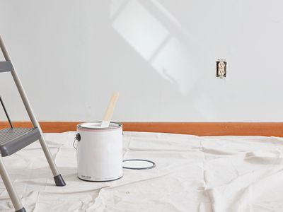 can of open paint on a drop cloth