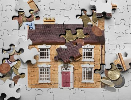 Illustration of puzzle pieces and coins forming the two dimensional image of a house