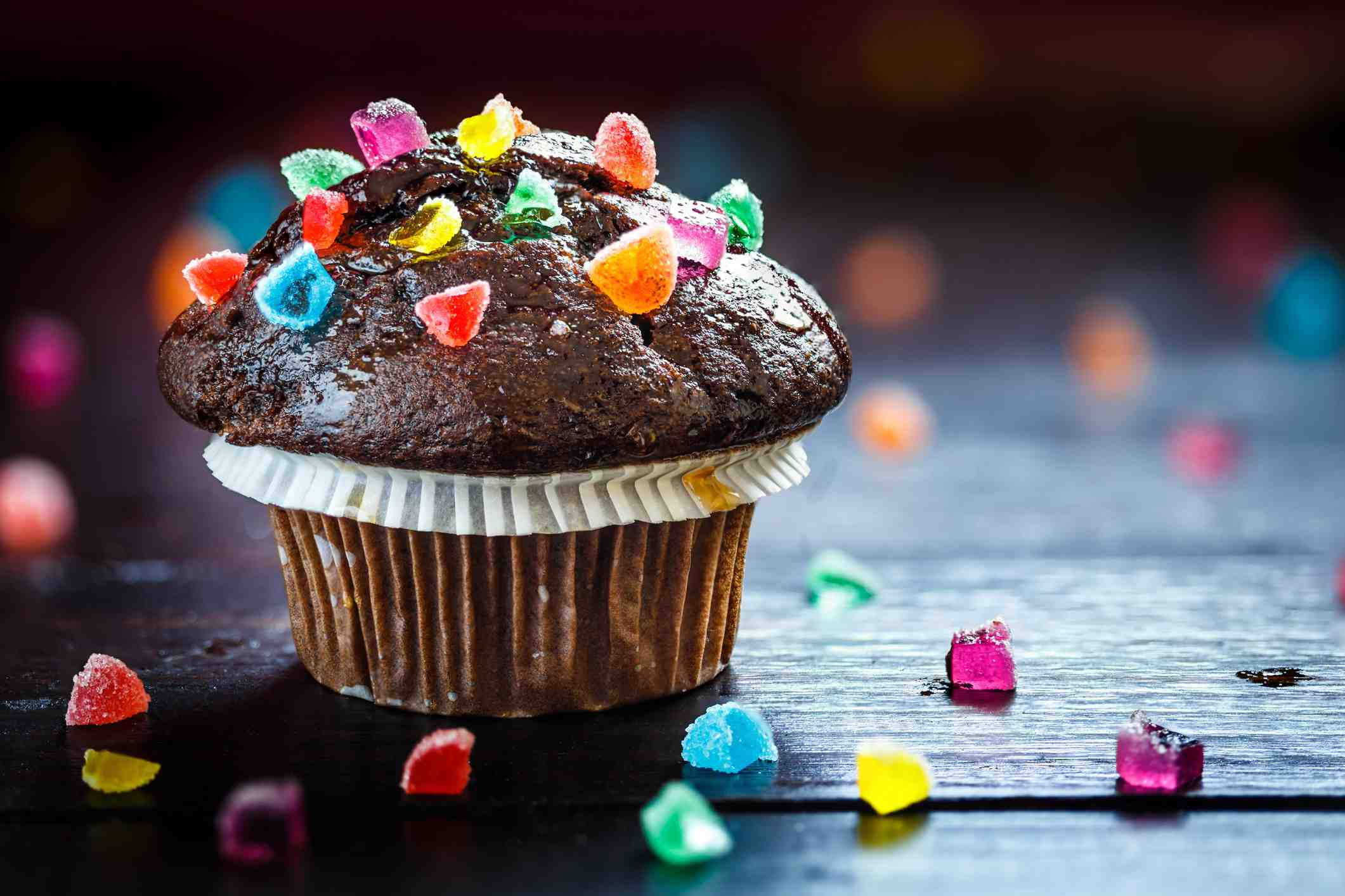 A chocolate cupcake with colorful jelly candies.