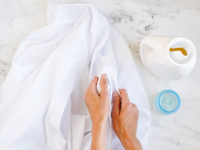 White lab coat being rubbed together with laundry detergent bottle on side