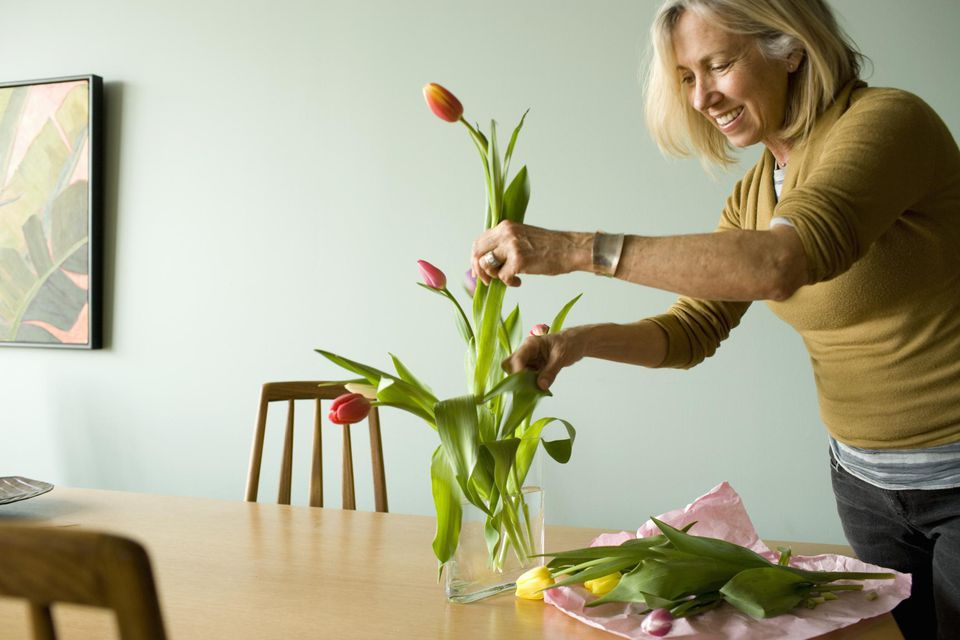 Woman arranging tulips in vase.
