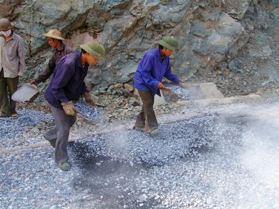 Workers building a tar-and-chip road.