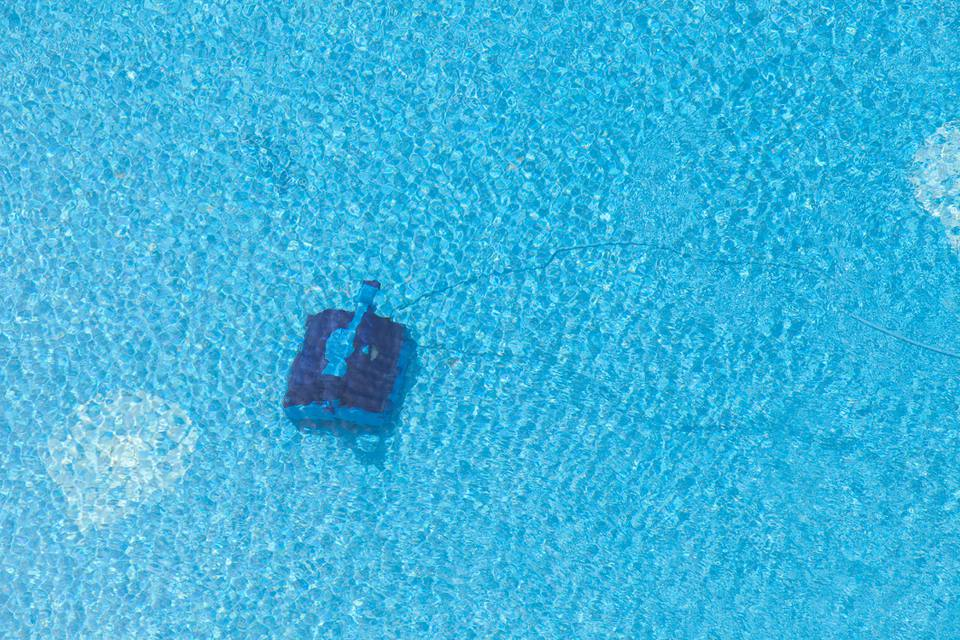 Robotic pool cleaner on bottom of pool