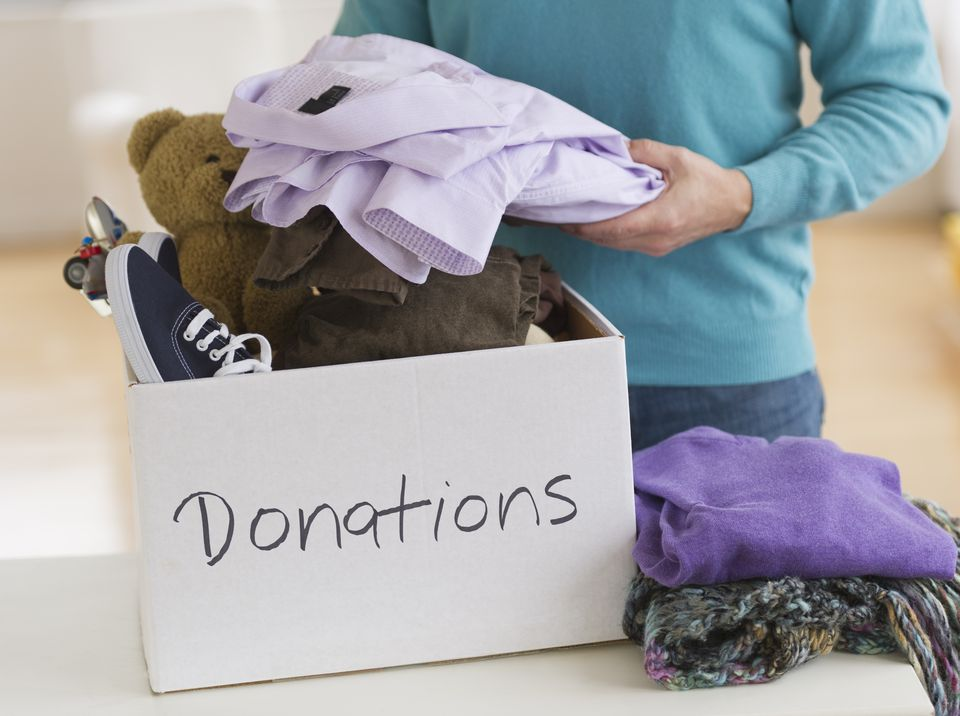 Woman filling a donation box with clothes and toys