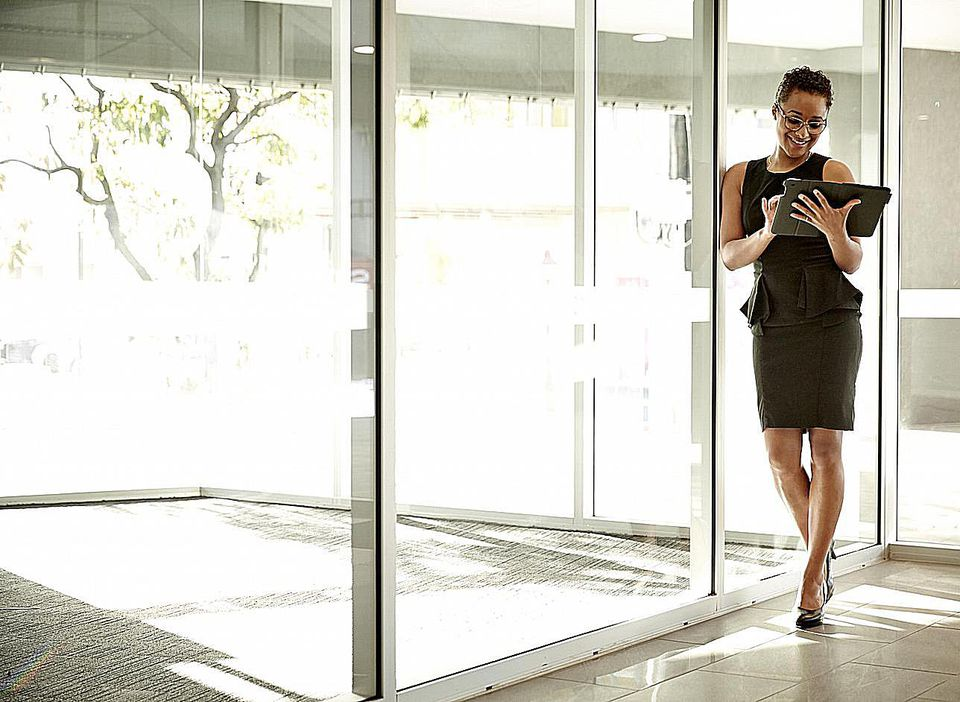 Woman at work on a tablet near glass doors leading to an atrium.