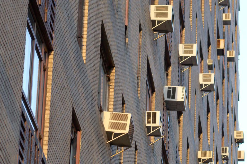 Air conditioners on apartment building at sundown