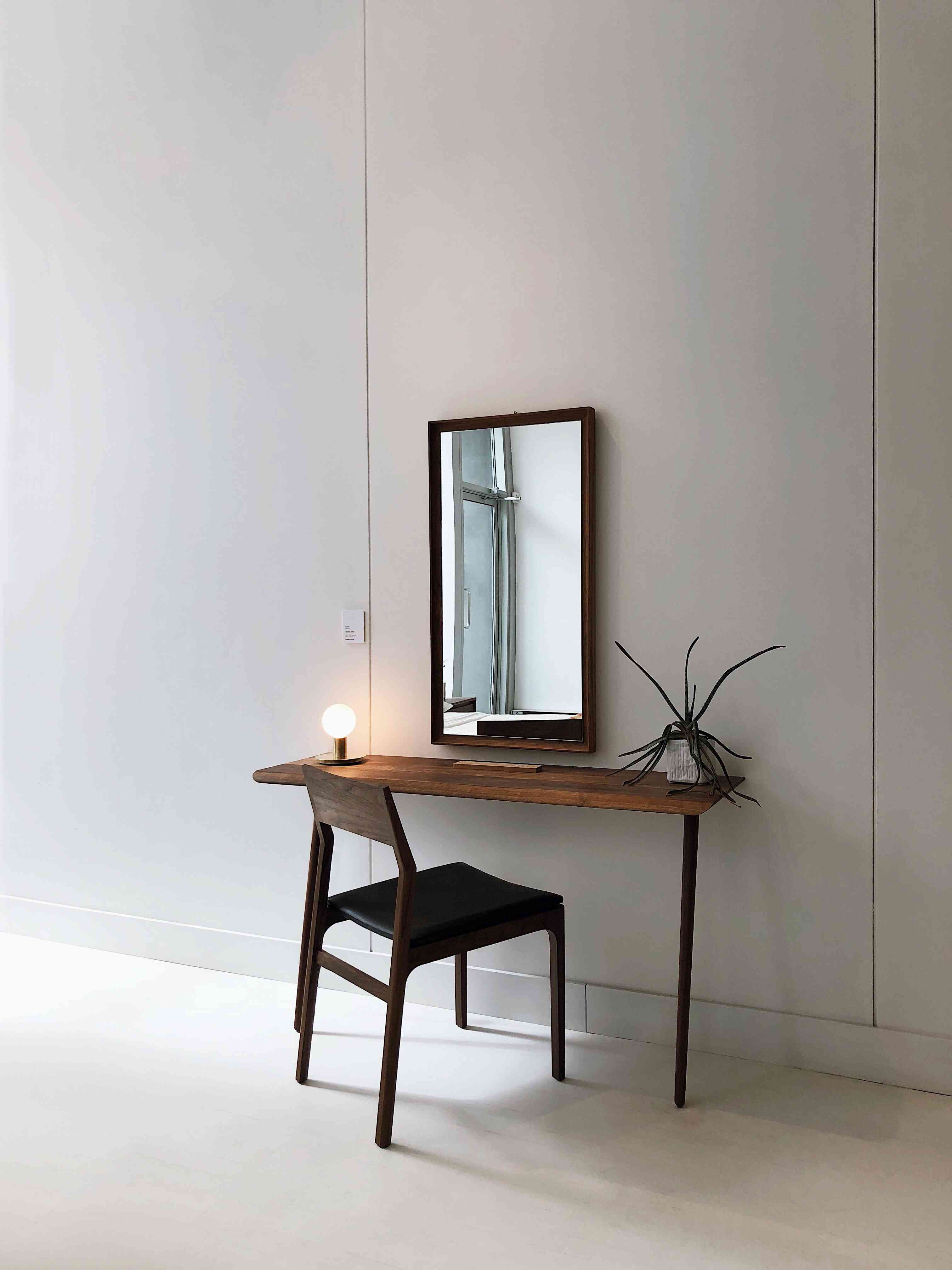 wood framed rectangular mirror over a desk and chair