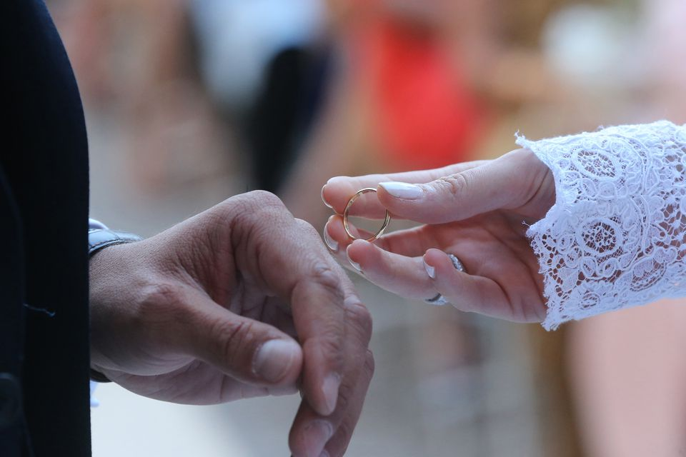 Close up of a couple exchanging wedding rings