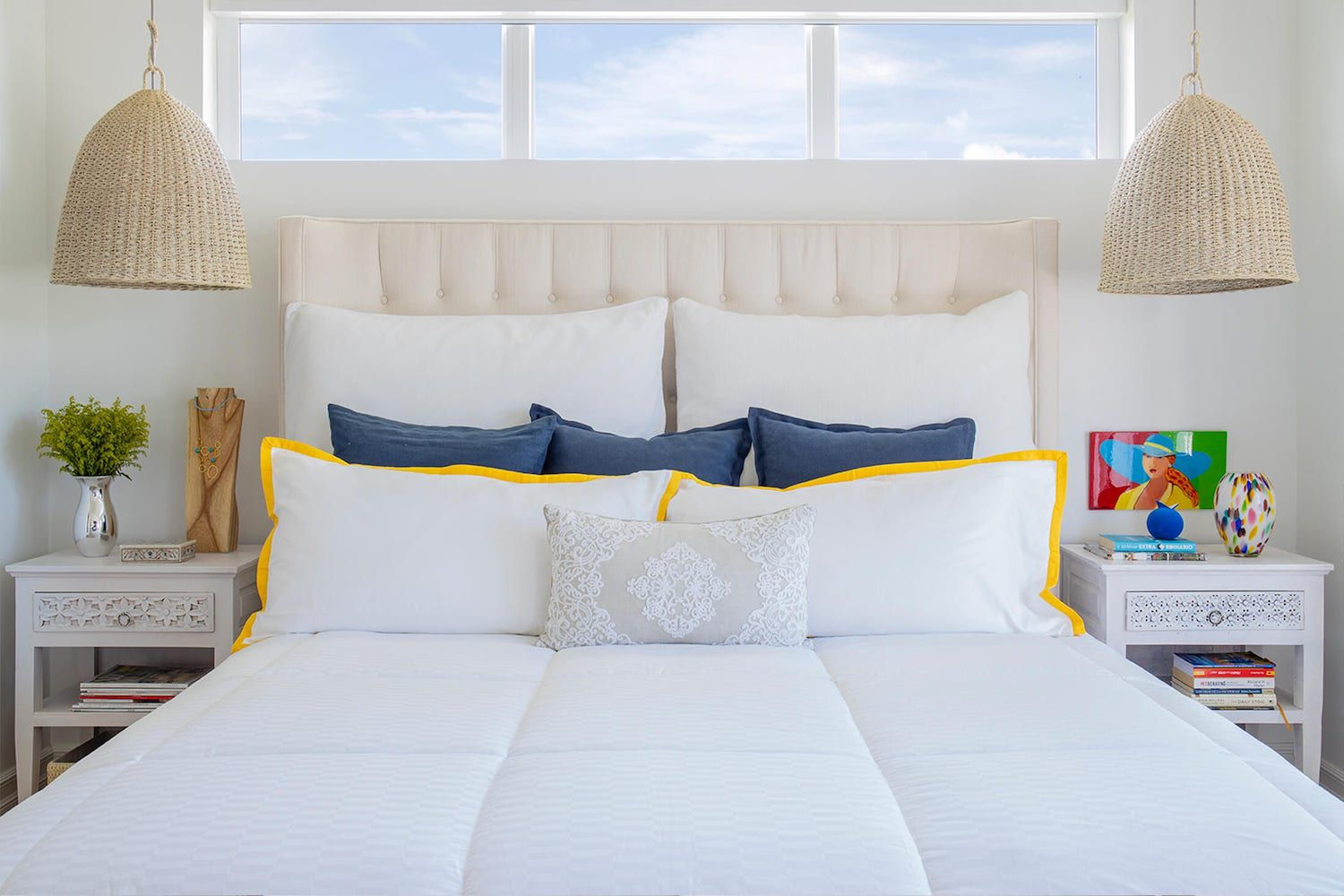 mostly white neutral bedroom with wicker rattan hanging lights, small pops of color, open windows above the bed