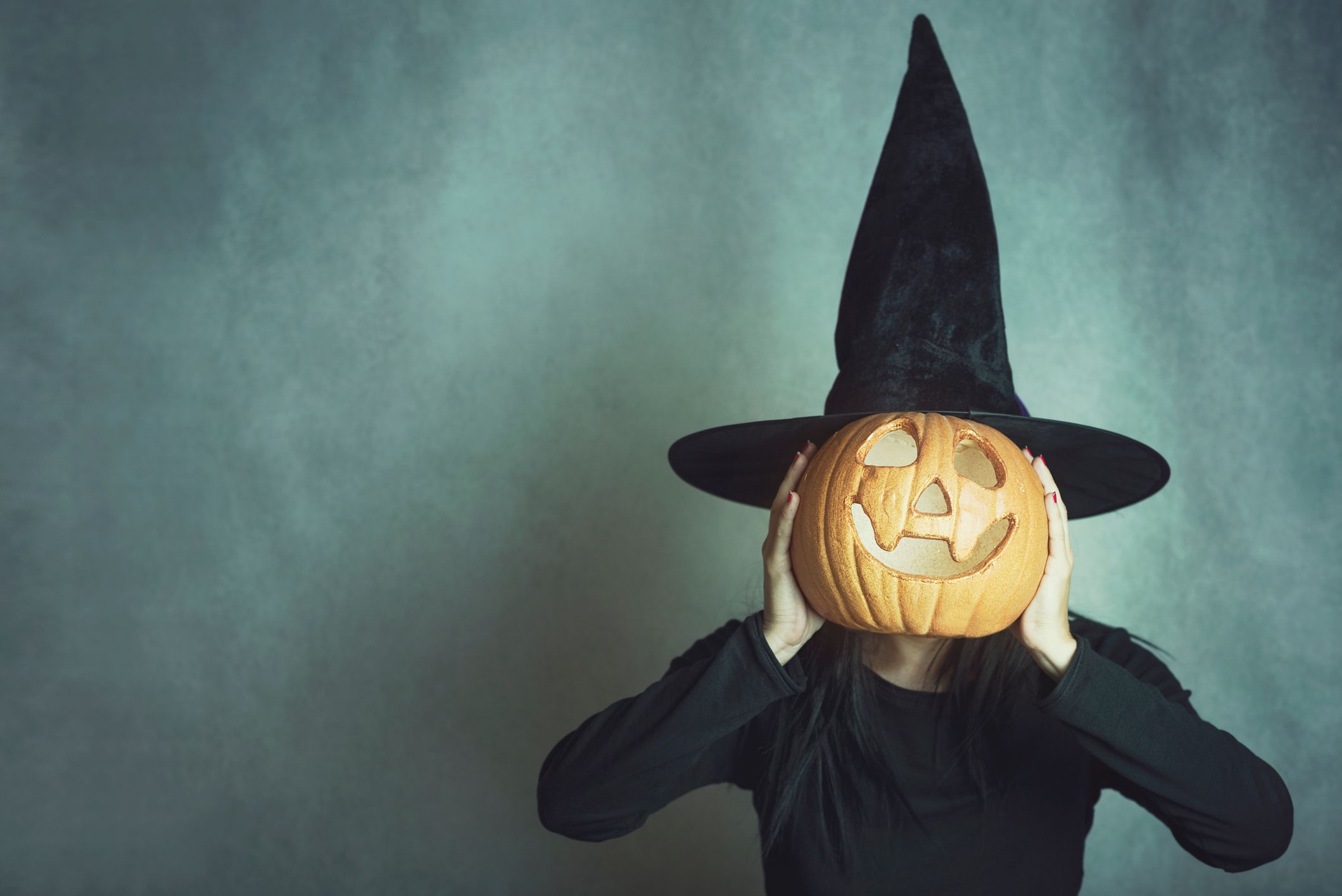 A woman wearing a witch hat holding a jack-o-lantern.