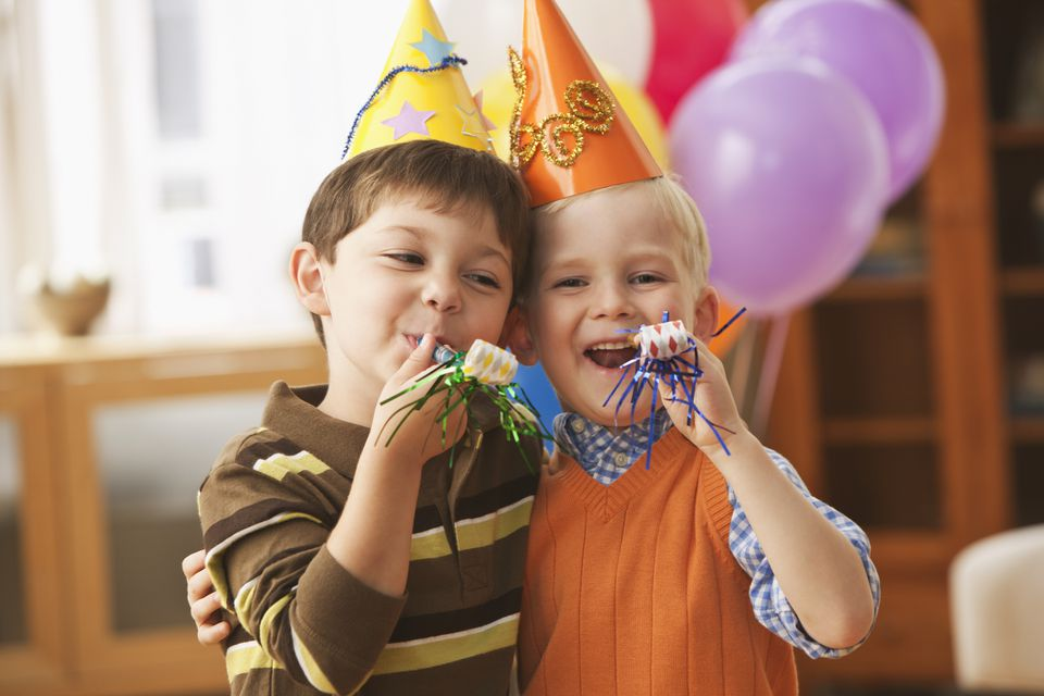boys blowing noise makers at party