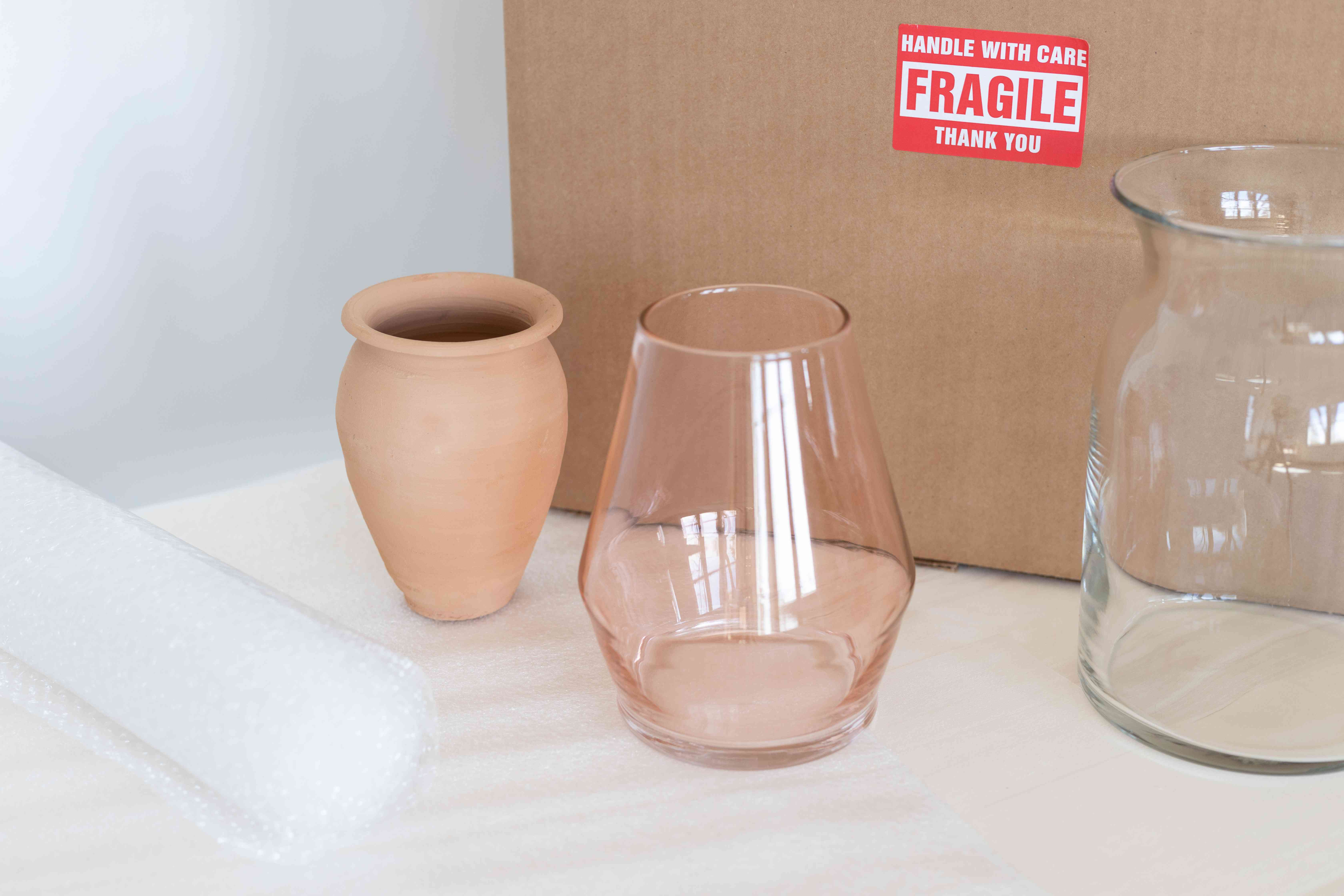 Glass and clay vases in front of moving box and bubble wrap