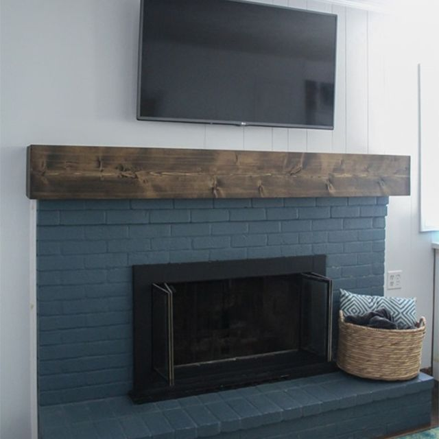 A blue fireplace with a TV above it