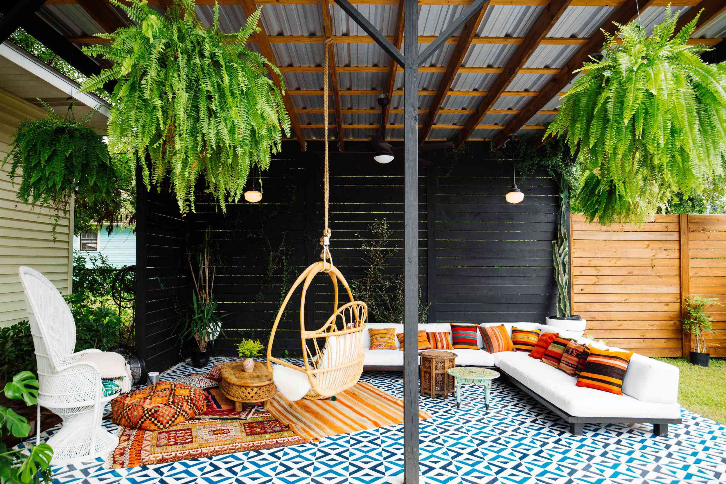Dabito's covered outdoor patio in New Orleans features hanging ferns, a swing chair, and a stenciled tile-look floor