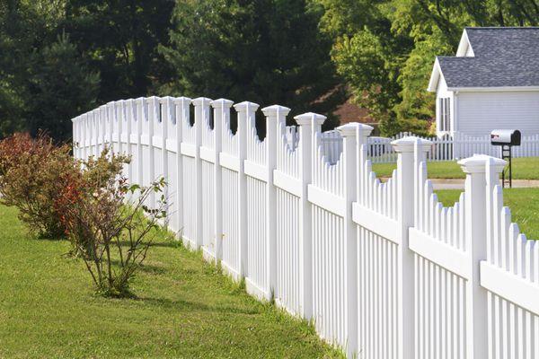 Ornate white vinyl fence running across a yard