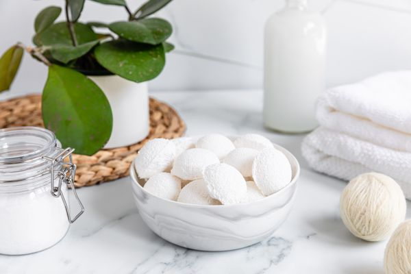 DIY laundry dryer balls in bowl next to glass jar of baking soda, folded towels and houseplant