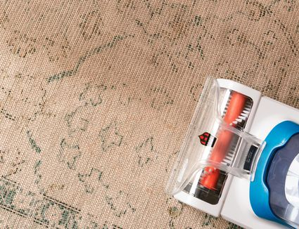 Steam cleaning machine massing over old tan patterned carpet