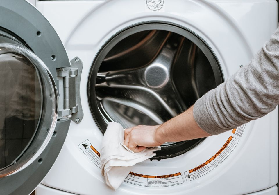 a person wiping down a washing machine