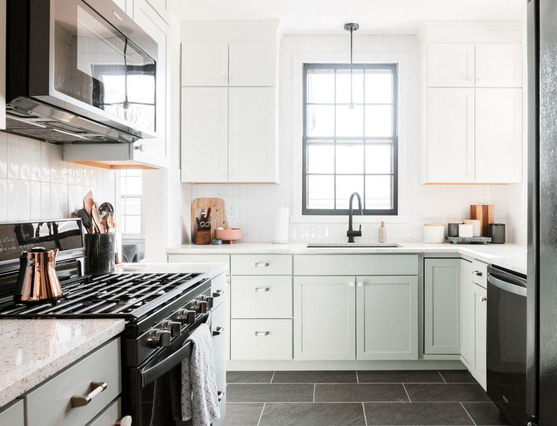 Cocina remodelada con piso de baldosas negras, gabinetes inferiores verdes y gabinetes superiores blancos. .