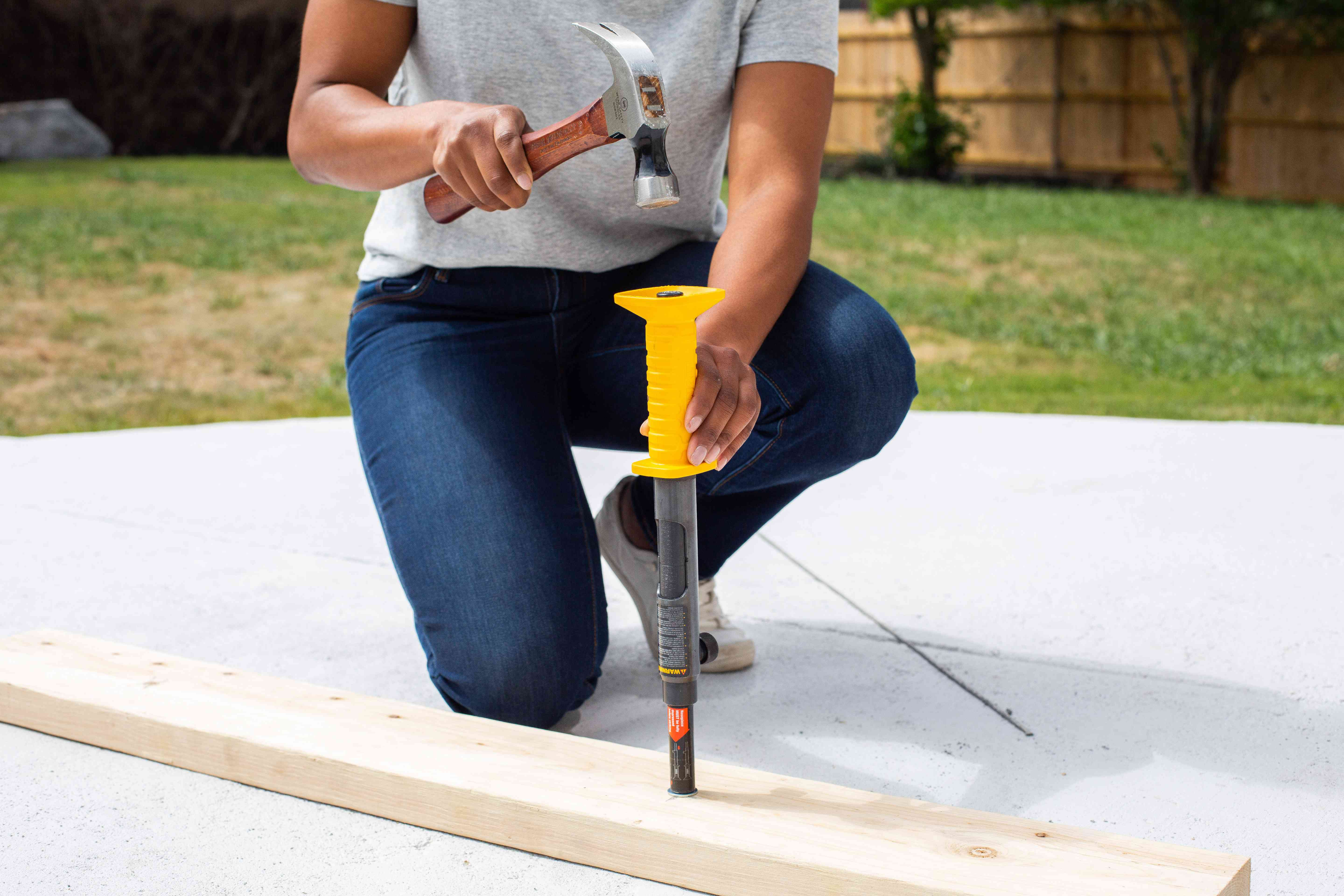 Hammer striking the concrete nail gun from above on wooden board