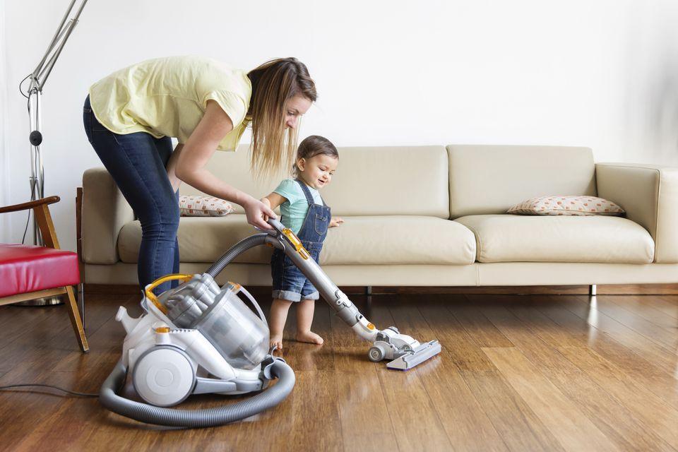 Woman and young boy wearing denim dungarees, standing in front of sofa, hoovering hardwood floor.
