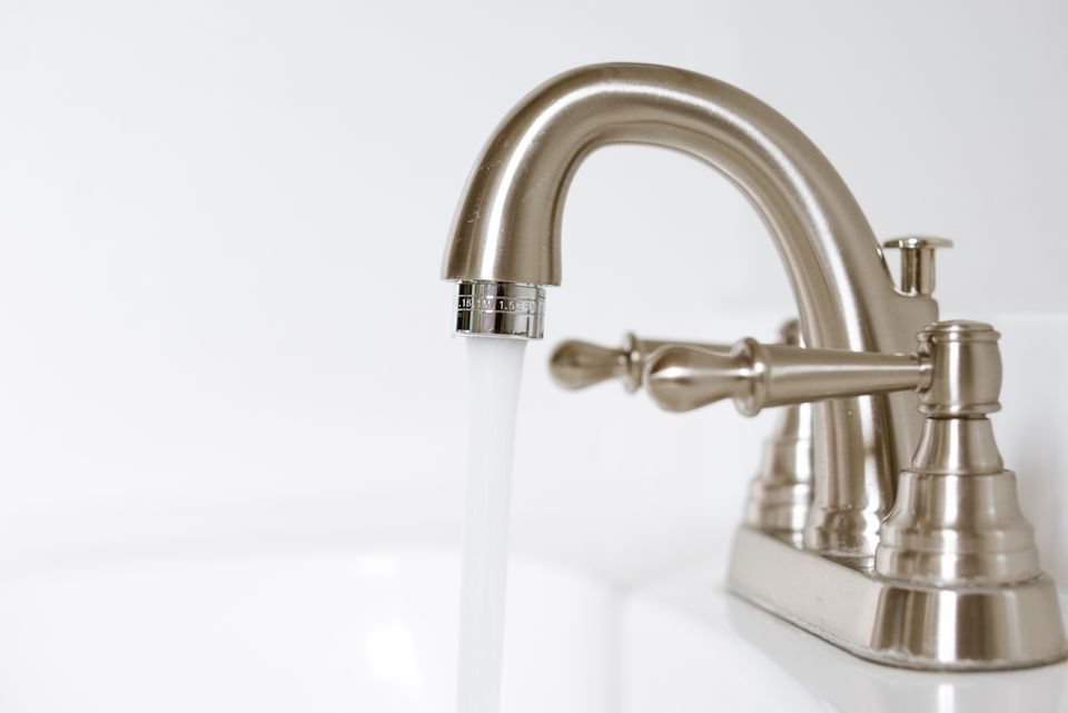 Silver faucet with a flow of running water and exposed aerator