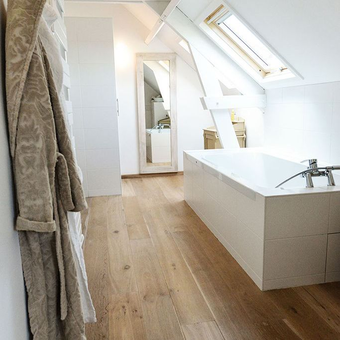slopped attic ceiling bathroom with window