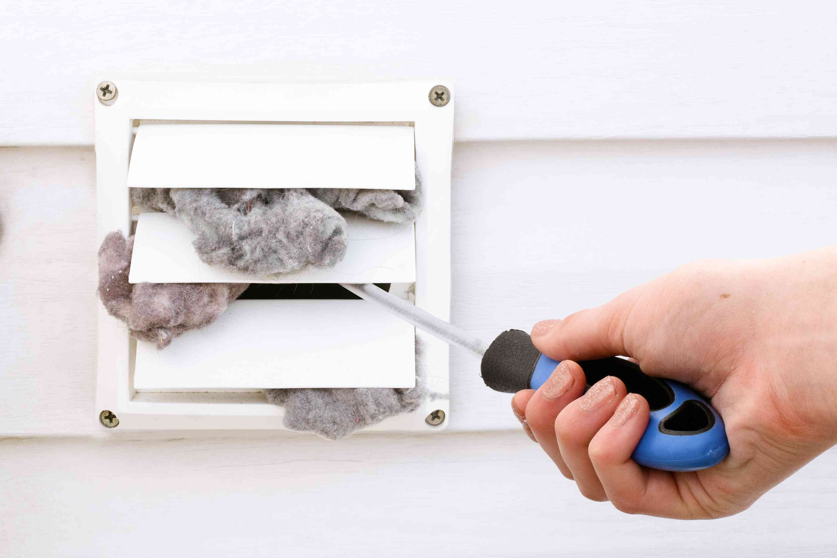 Outside dryer vent slats filled with lint being opened manually with vent brush