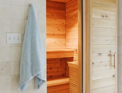 Exterior shot of steam room in someone's home, with towel hanging up next to door.