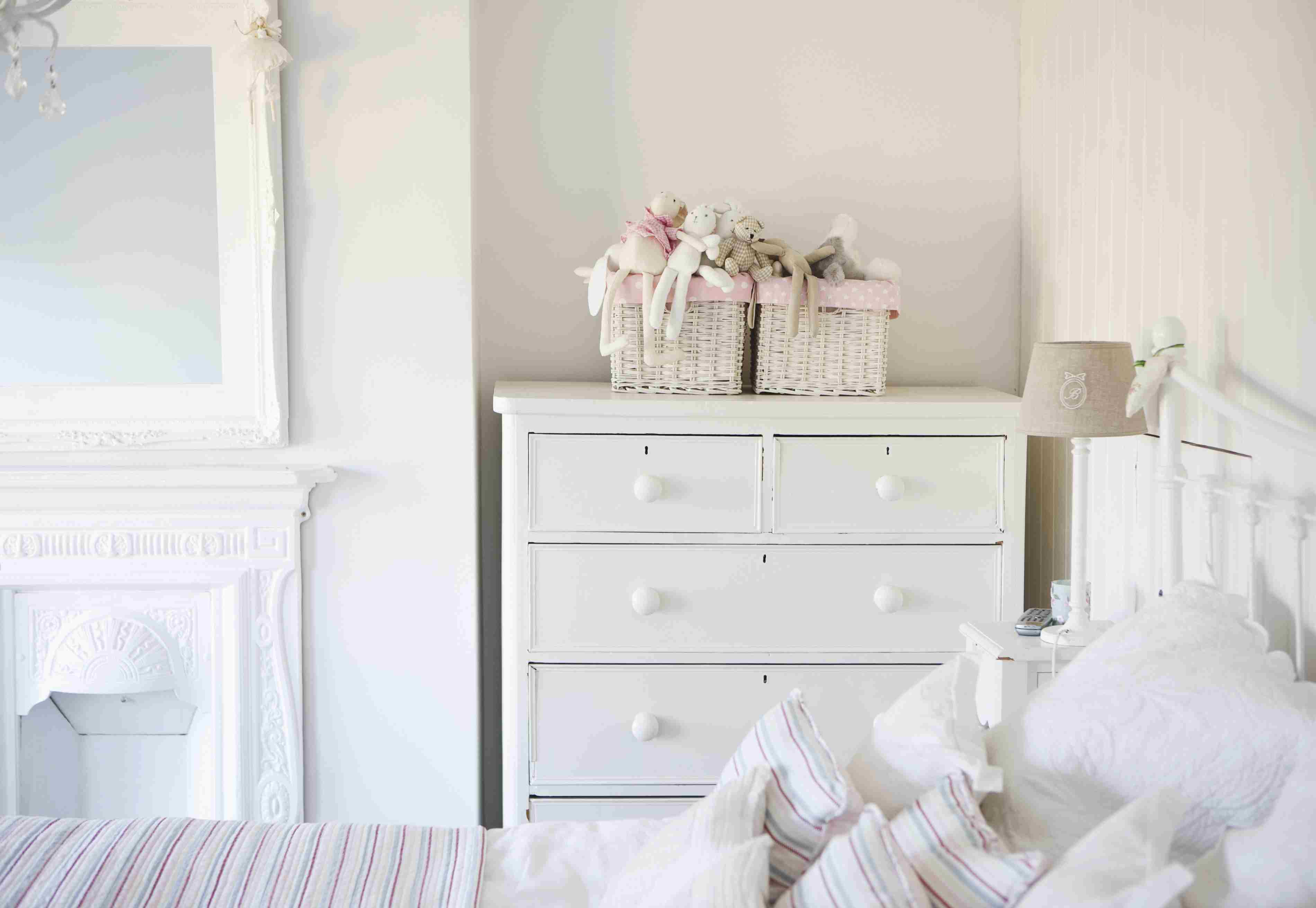 Shabby chic bedroom in white with dresser, bed, and mirror.
