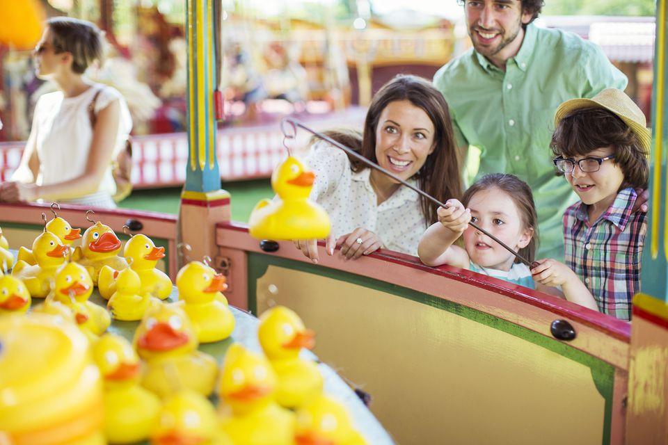 Parents With Two Children Having Fun With Fishing Game in Amusement Park